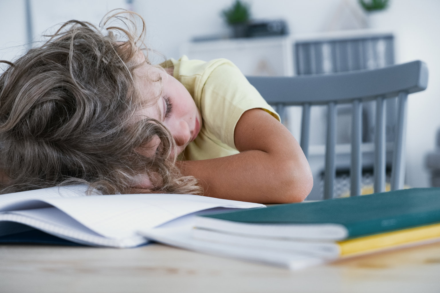 Close-up of a tired kid sleeping with his head rested on a table with a book.